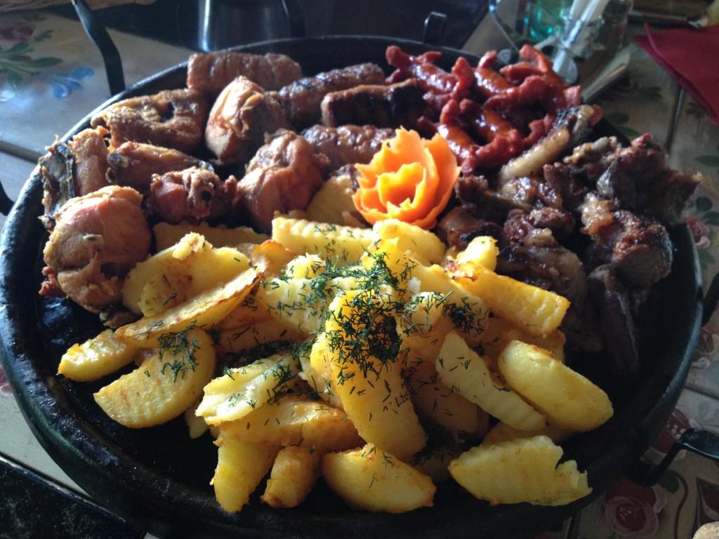 Friptura vita, friptura miel, friptura porc, cirnaciori, cartofi la cuptor (Roast beef, roast lamb, roast pork, sausages, and baked potatoes)